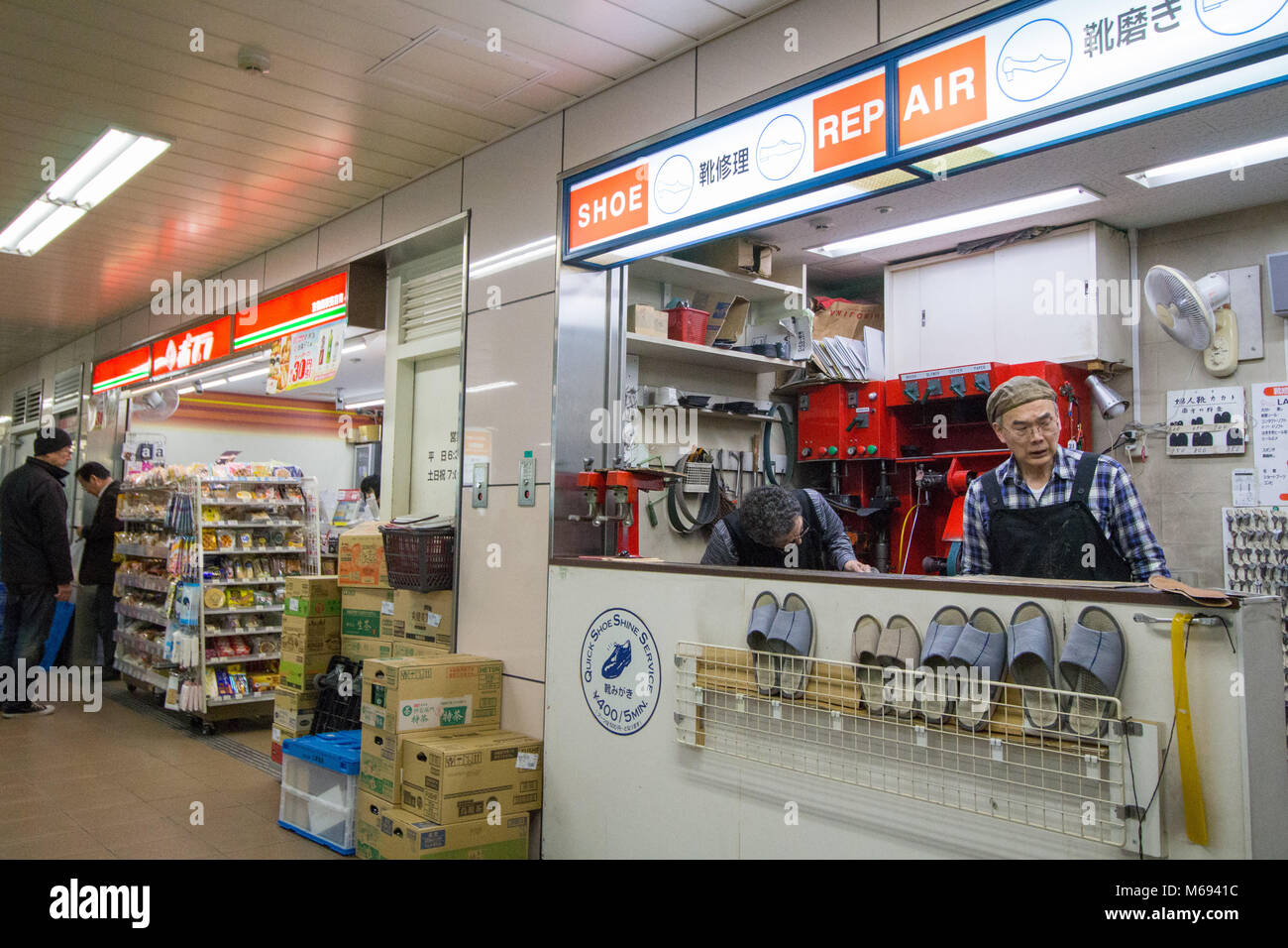 The busy concourse of Osaka train station. A shoe repair stall on the concourse of the station - Stock Image