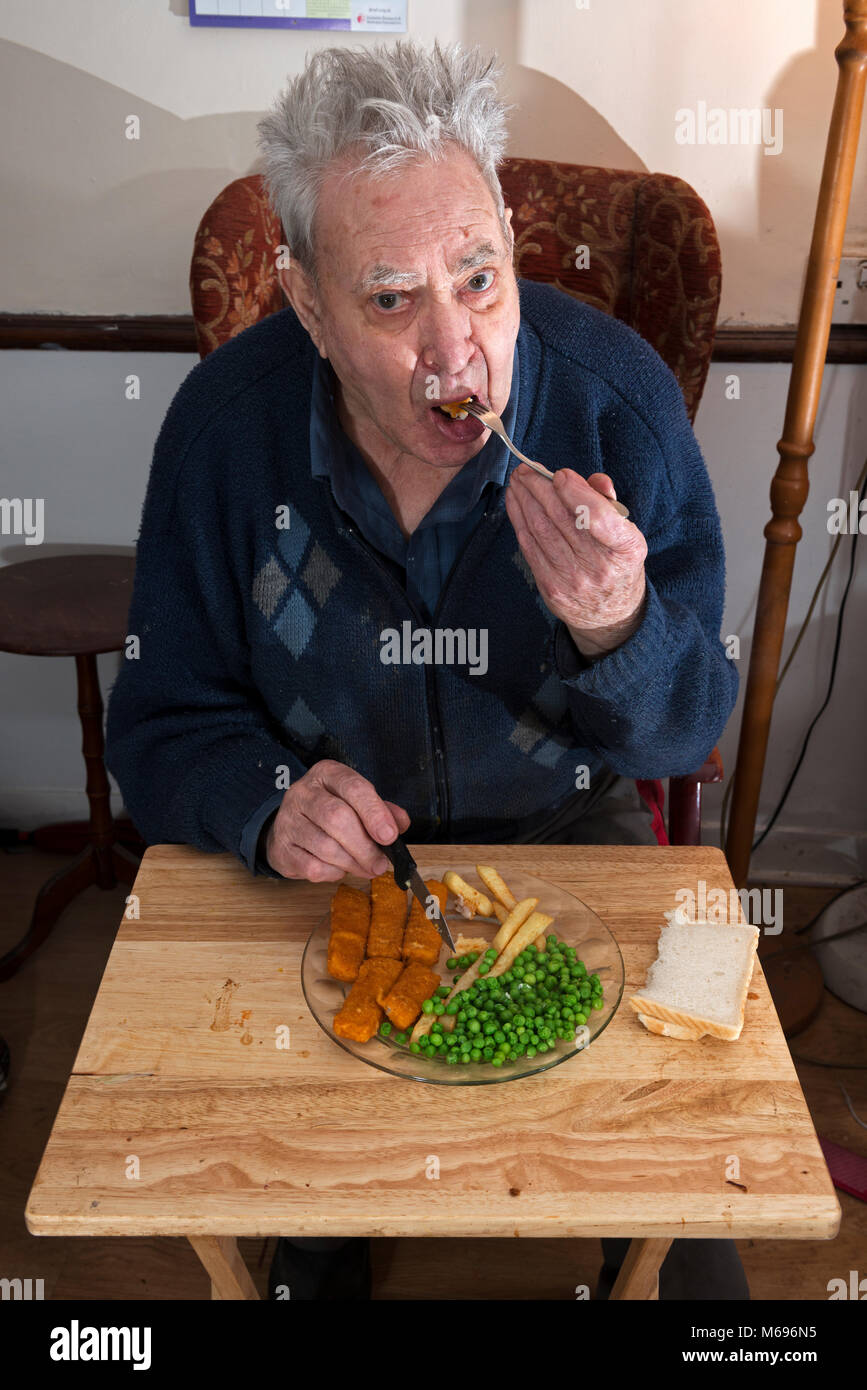 Elderly man eating fish fingers, chips and peas for his lunch - Stock Image