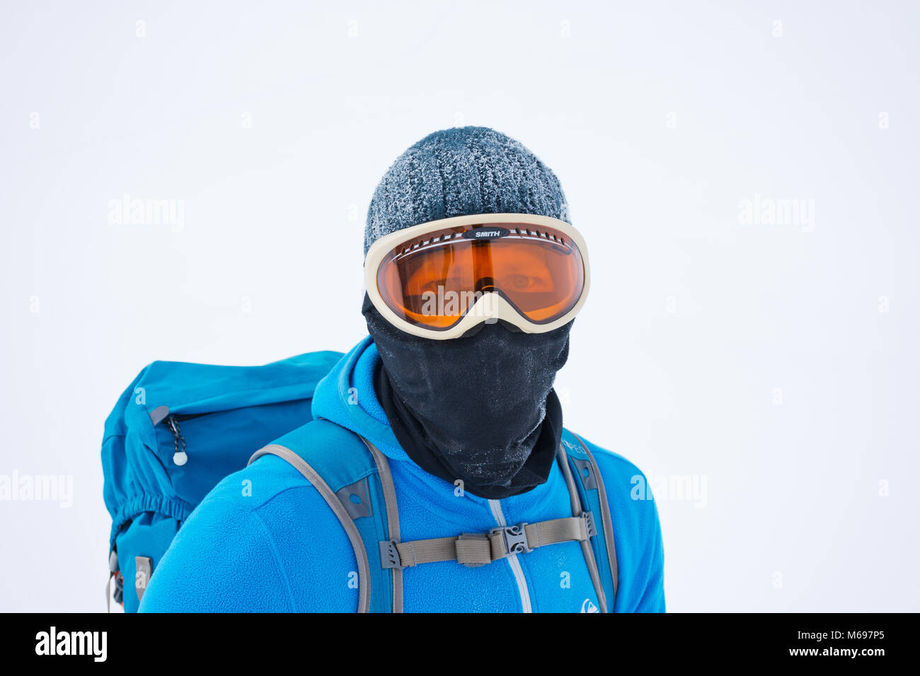 Portrait of ski mountaineer covering his face, with snow white background on a cold foggy winter day, wearing ski - Stock Image