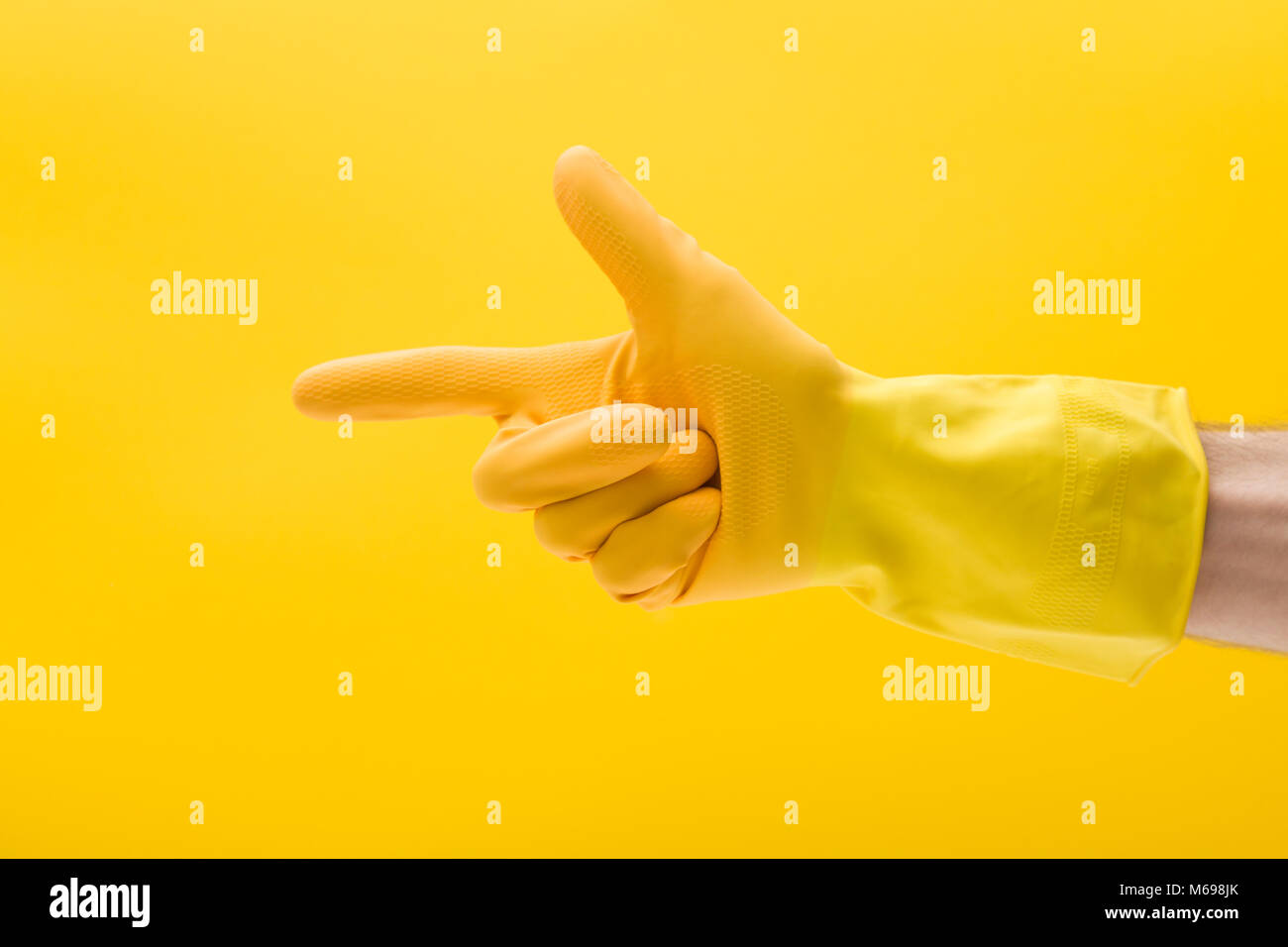 Pointing hand gesture made by a hand in a yellow rubber cleaning glove - Stock Image