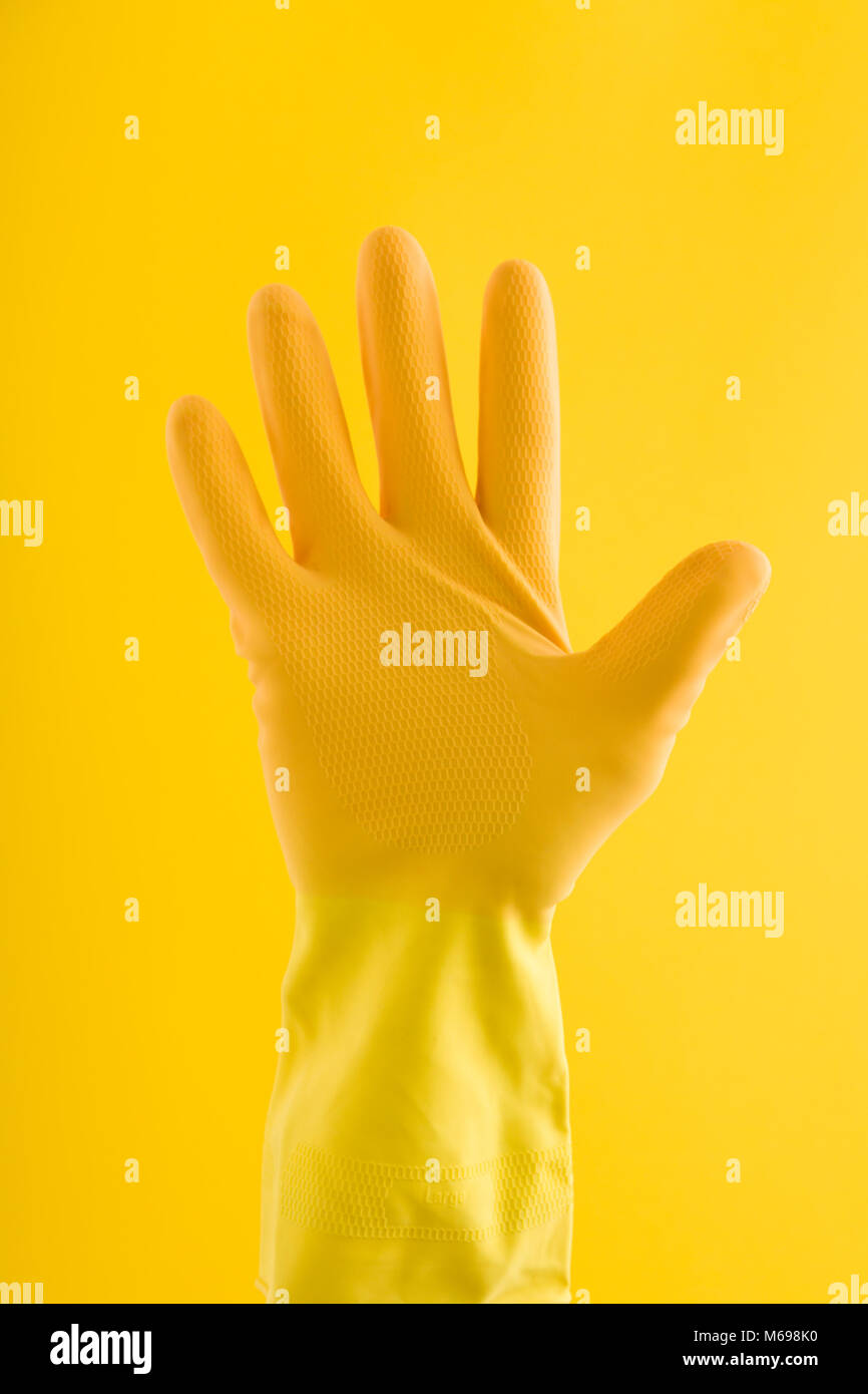Hand in a yellow rubber cleaning glove - Stock Image