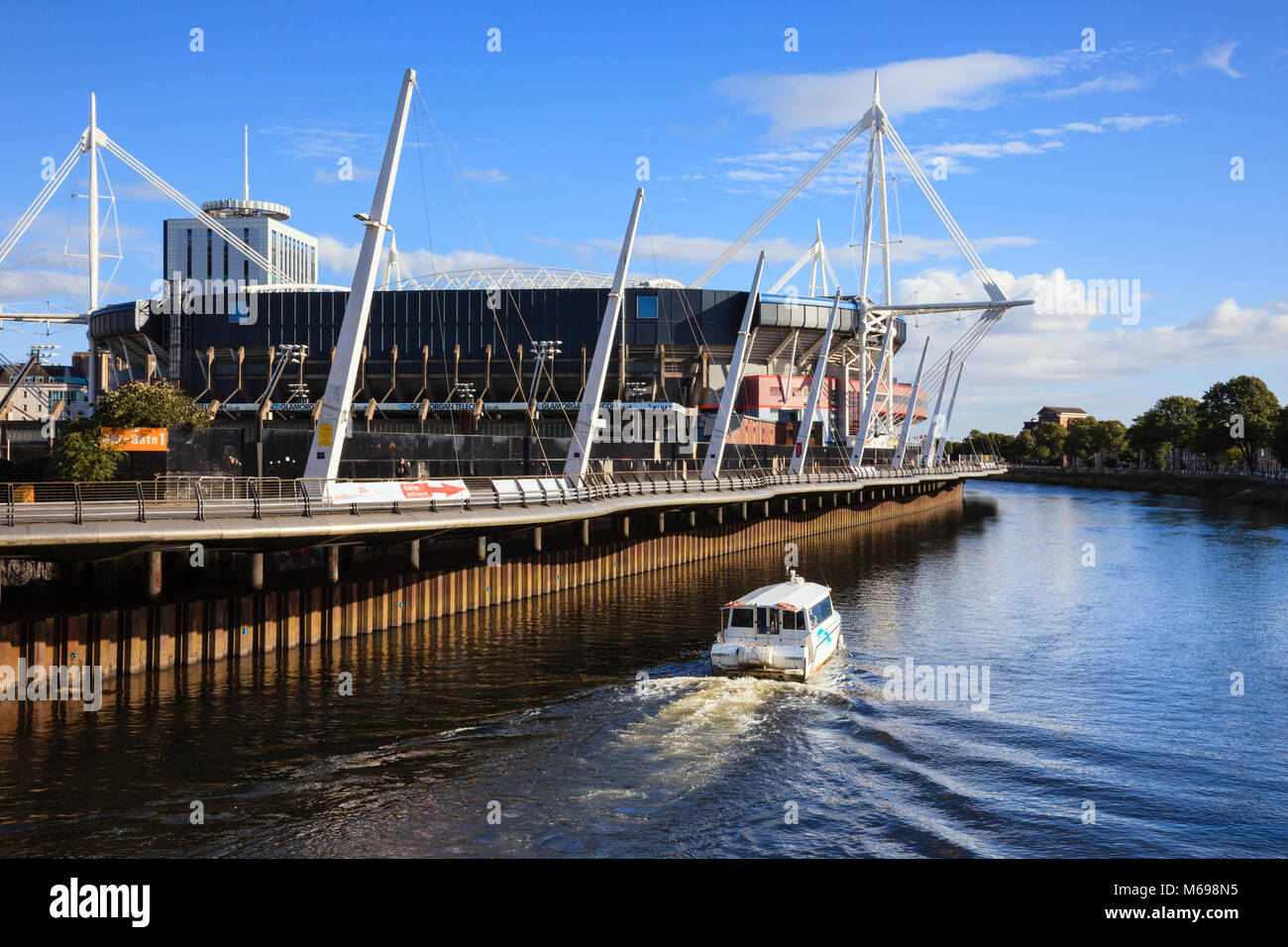 Cardiff Principality Stadium football and rugby venue with watertaxi passing on the River Taff. Cardiff (Caerdydd) - Stock Image