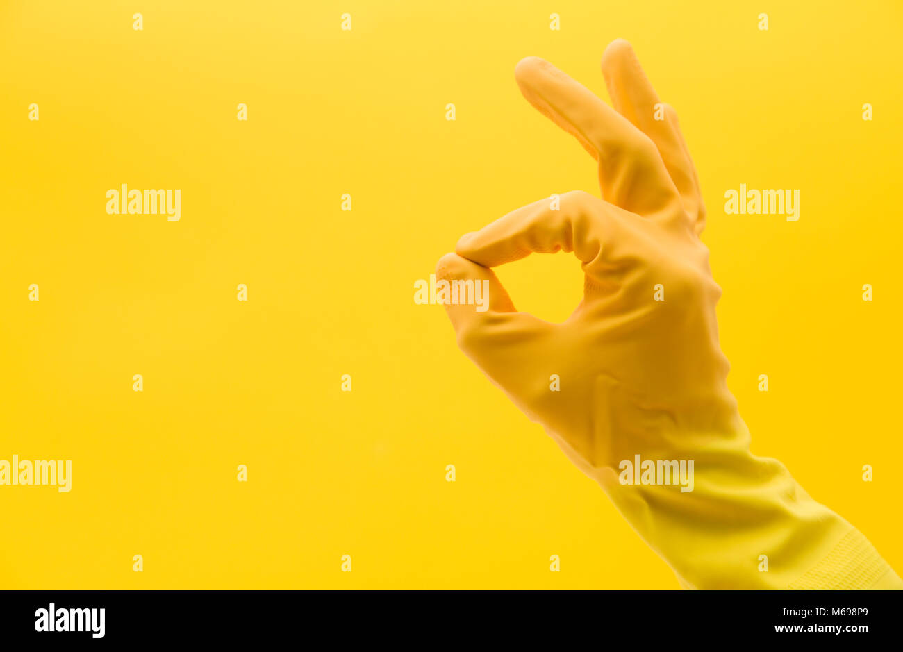 Okay hand gesture made by a hand in a yellow rubber cleaning glove - Stock Image