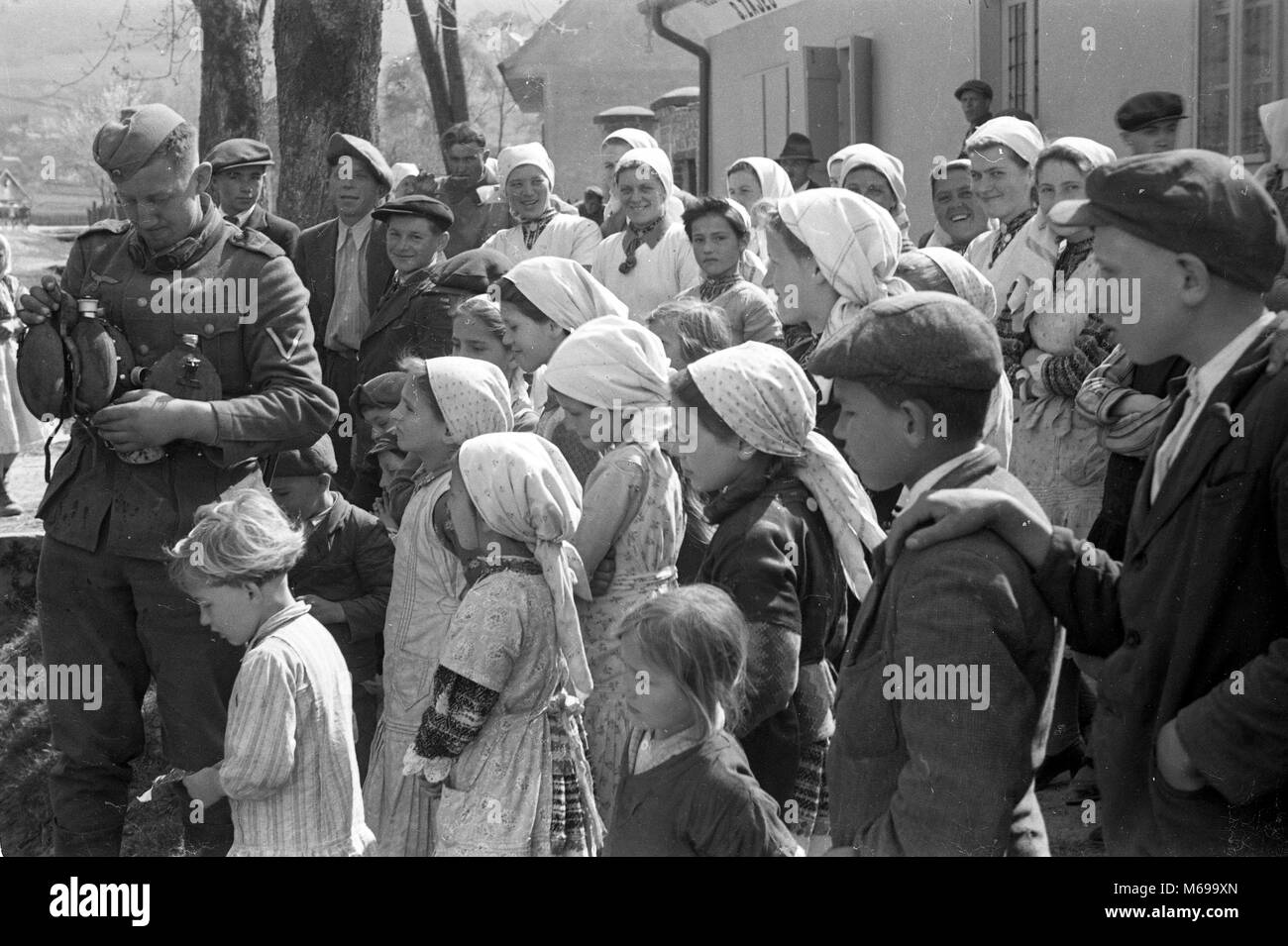 Local people watching German soldiers filling water bottles in Yugoslavia in April 1941 during WW2 German invasion - Stock Image