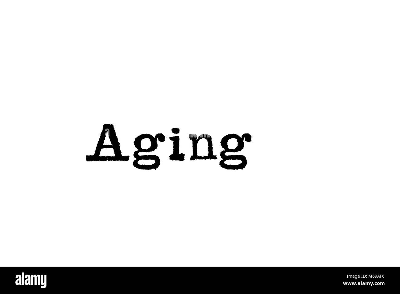 The word Aging from a typewriter on a white background - Stock Image