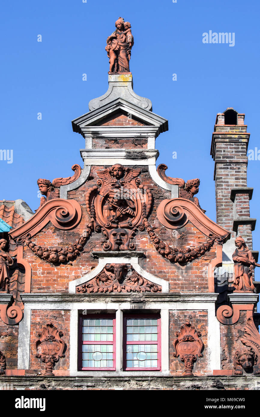 Flute Player / de Hel, terracotta sculptures, festoons and volutes decorating gable of 17th century baroque house - Stock Image