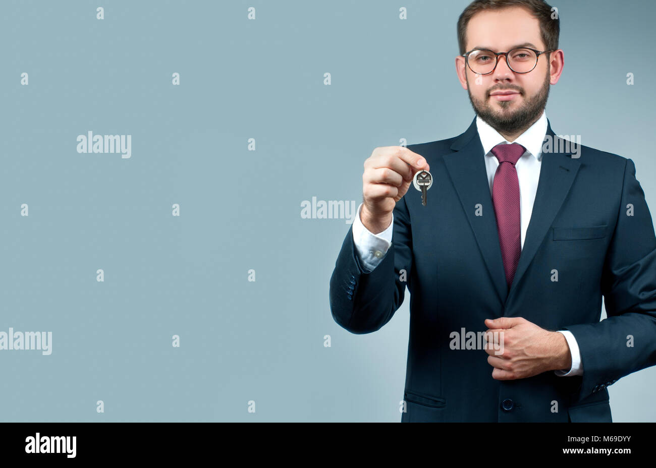 Businessman or real estate agent is holding keys. Finance Savings concept - Stock Image