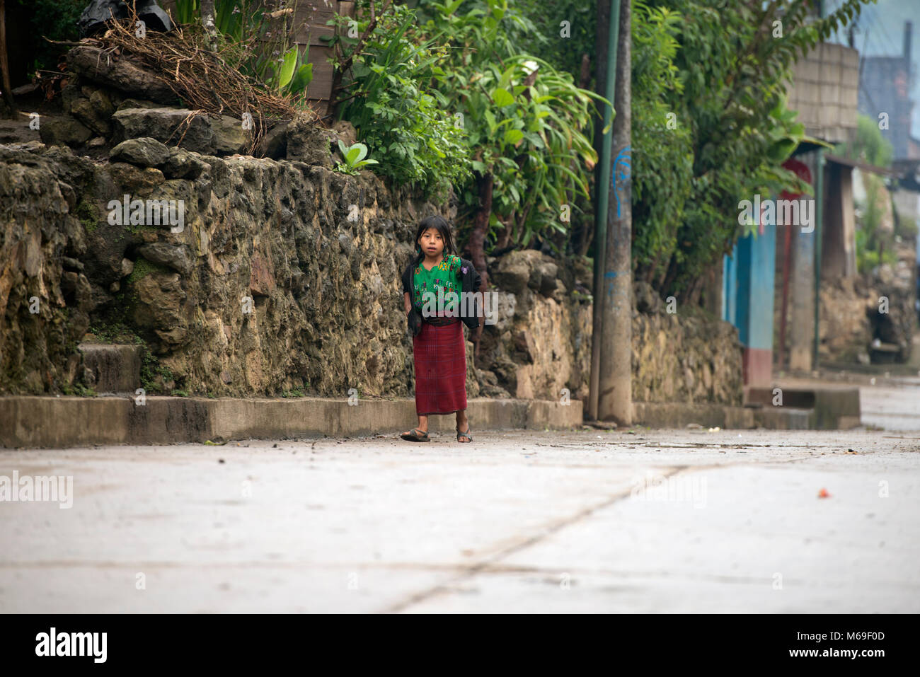 A young, indigenous Ixil Maya girl in traditional dress walking along the street in the rain in San Gaspar Chajul, - Stock Image
