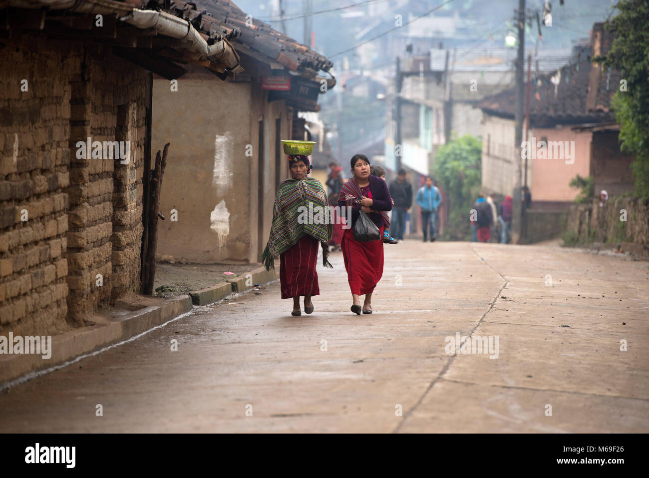 Ethnic, indigenous Ixil Maya women in traditional clothing walking home along the street in the rain in San Gaspar - Stock Image
