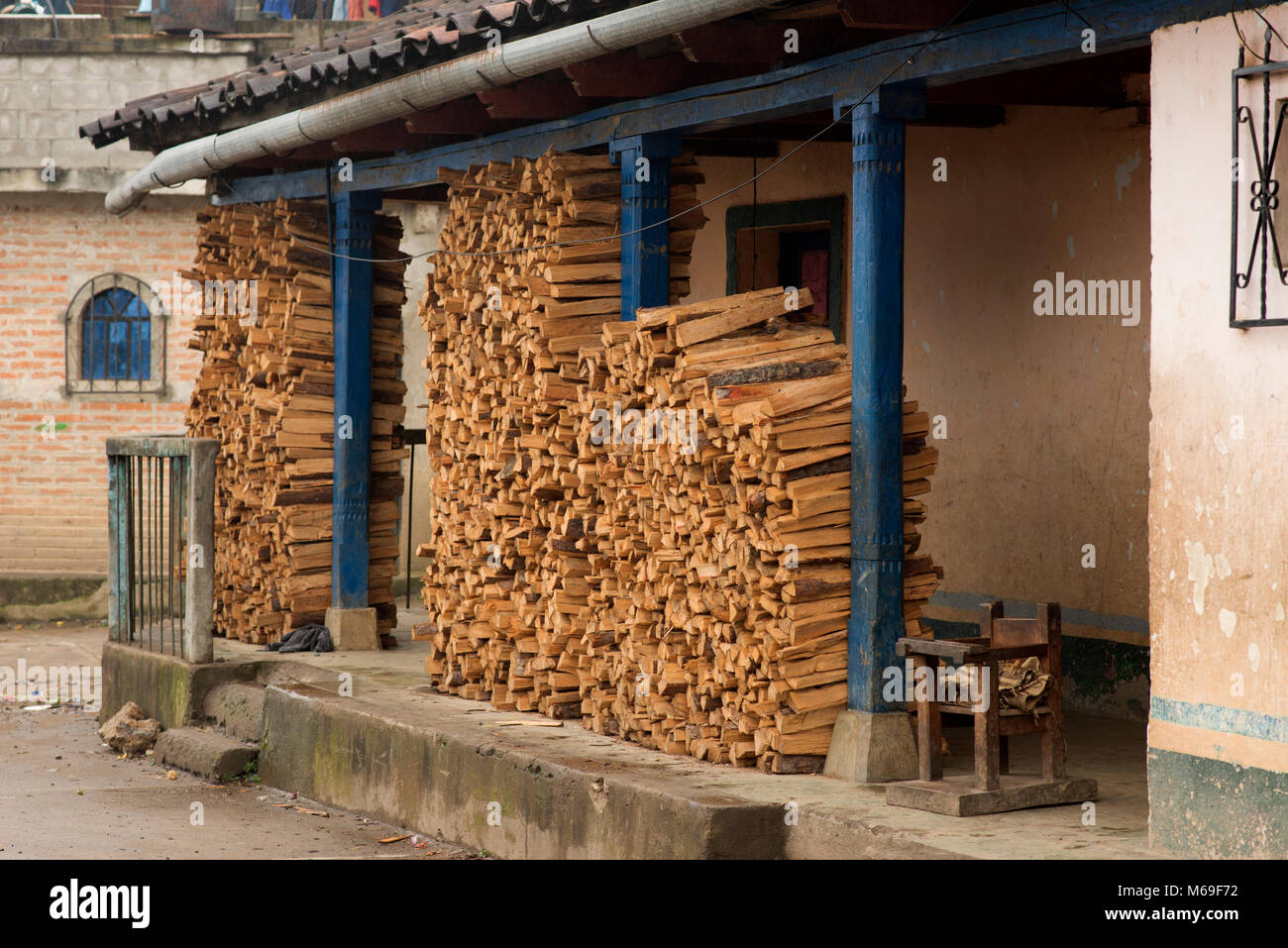 Firewood is piled high outside an Ixil house to heat it year round. San Gaspar Chajul, Ixil Triangle, Guatemala. - Stock Image