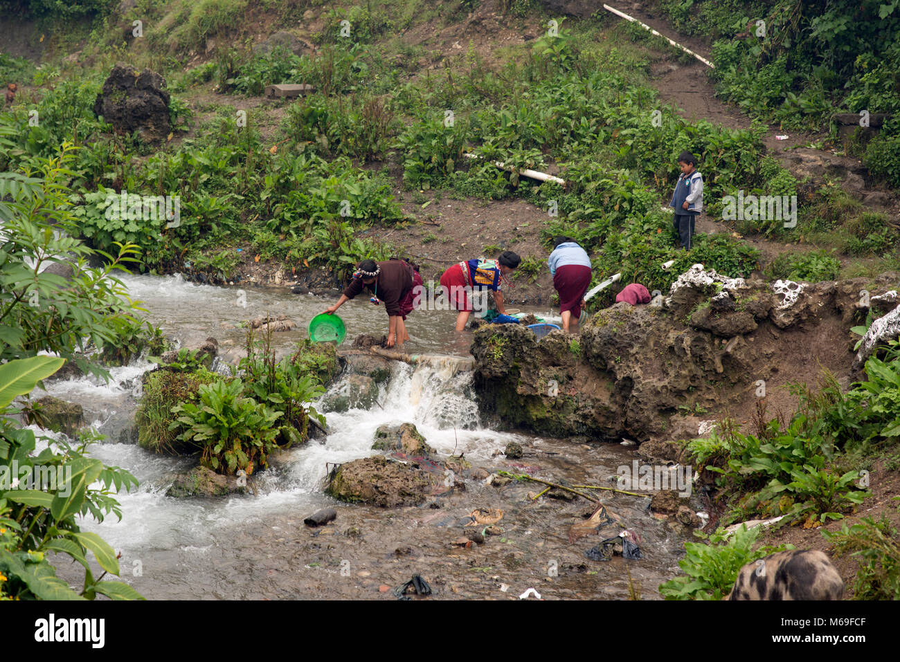Indigenous ethnic Ixil Maya women doing laundry in a river in San Gaspar Chajul, Ixil Triangle, Guatemala. - Stock Image