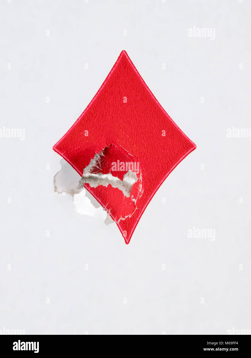 Shooted card. Red diamonds sign close up with a bullet hole - Stock Image