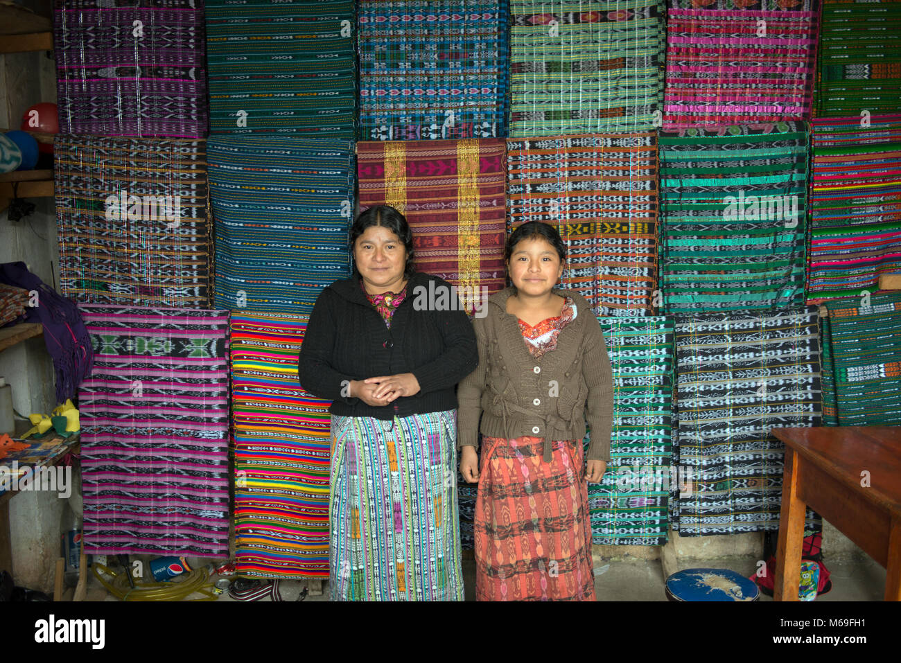 An indigenous ethnic Ixil Maya woman and her daughter selling colourful fabric in the market. San Gaspar Chajul, - Stock Image