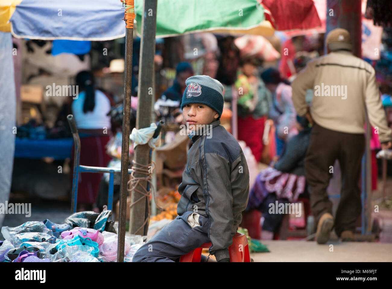 A young indigenous ethnic Ixil Maya boy selling shoes in the market. San Juan Cotzal, Ixil Triangle, Guatemala. - Stock Image