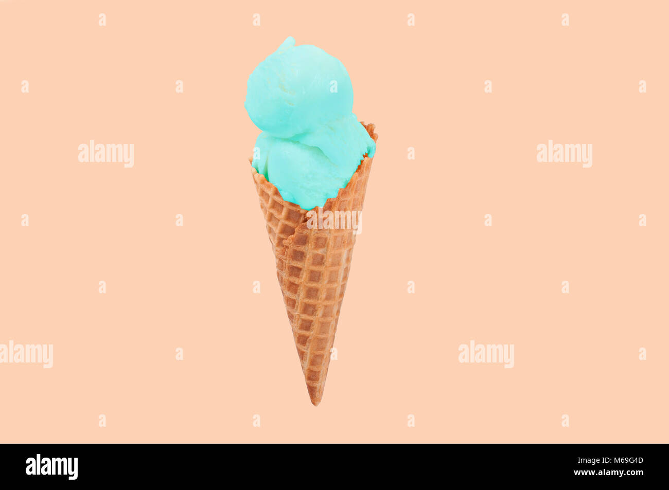 Pistachio ice cream cone on faded pastel color background. Ice cream in wafer cup. - Stock Image