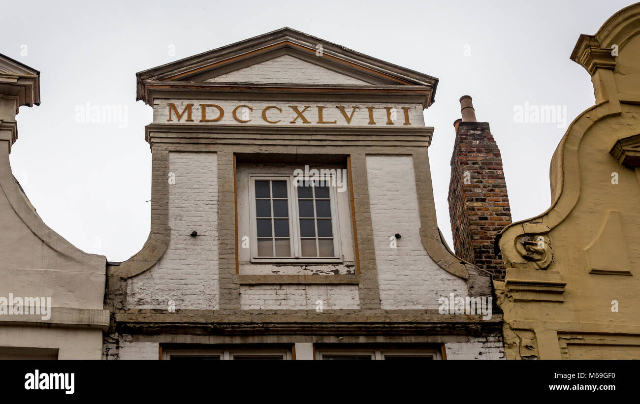 Palladian shaped roof facade with the date 1748 displayed in Roman Numerals over a square window frame in the architectural Stock Photo
