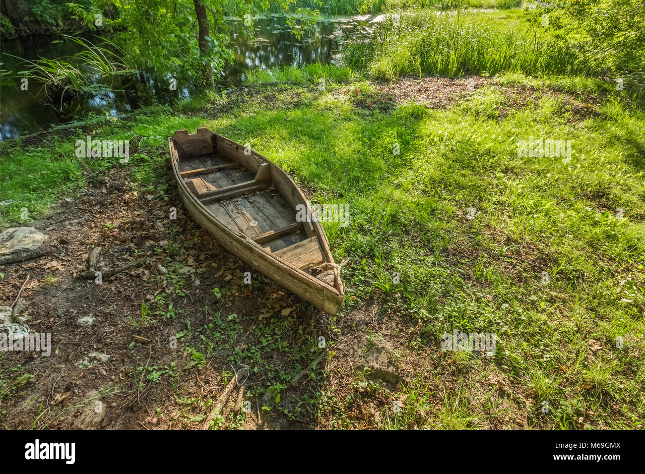 The old forgotten boat does not bank the swamp among the bushes and grass - Stock Image