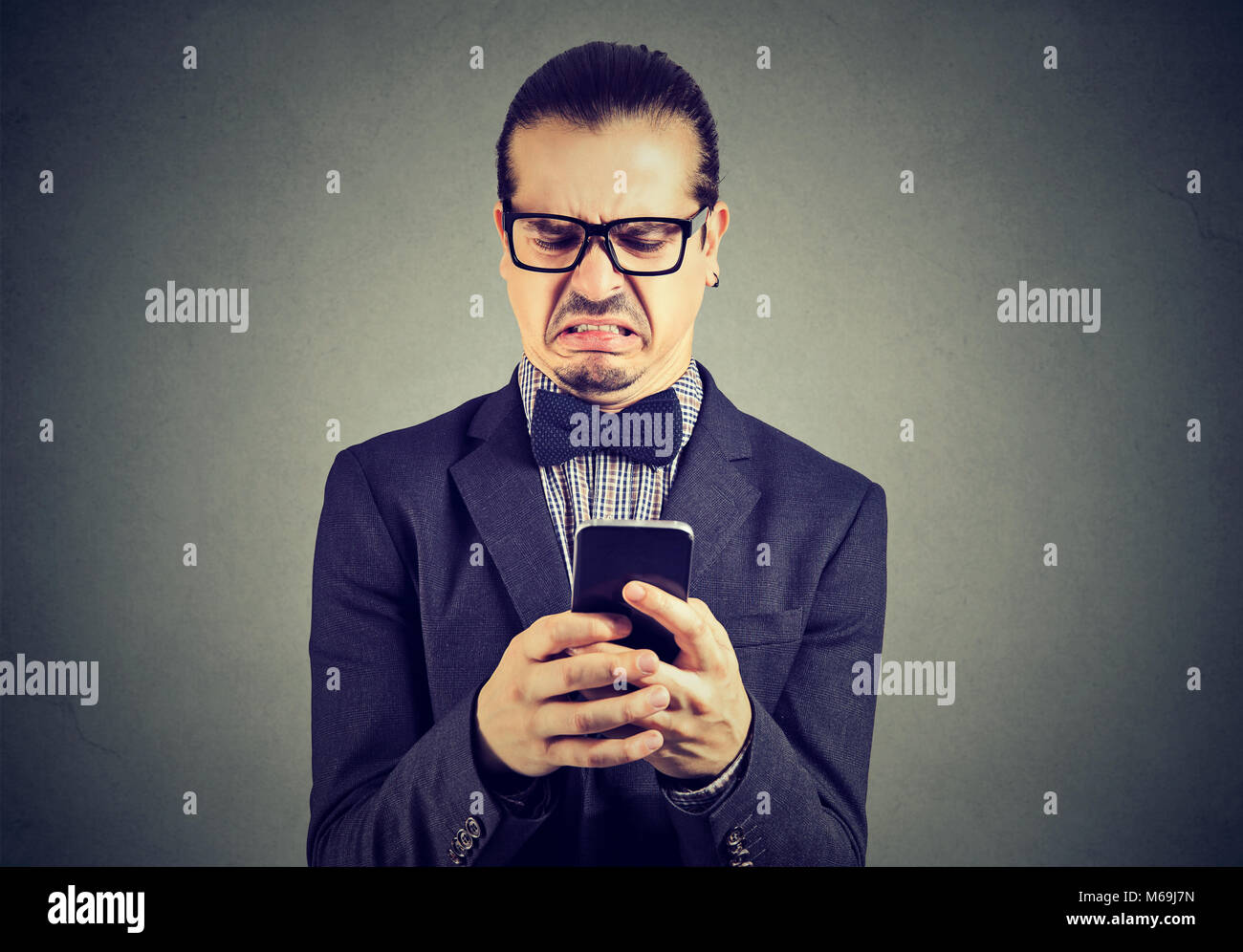 Young formal man in glasses and suit surfing smartphone with feeling of disgust being offended. - Stock Image