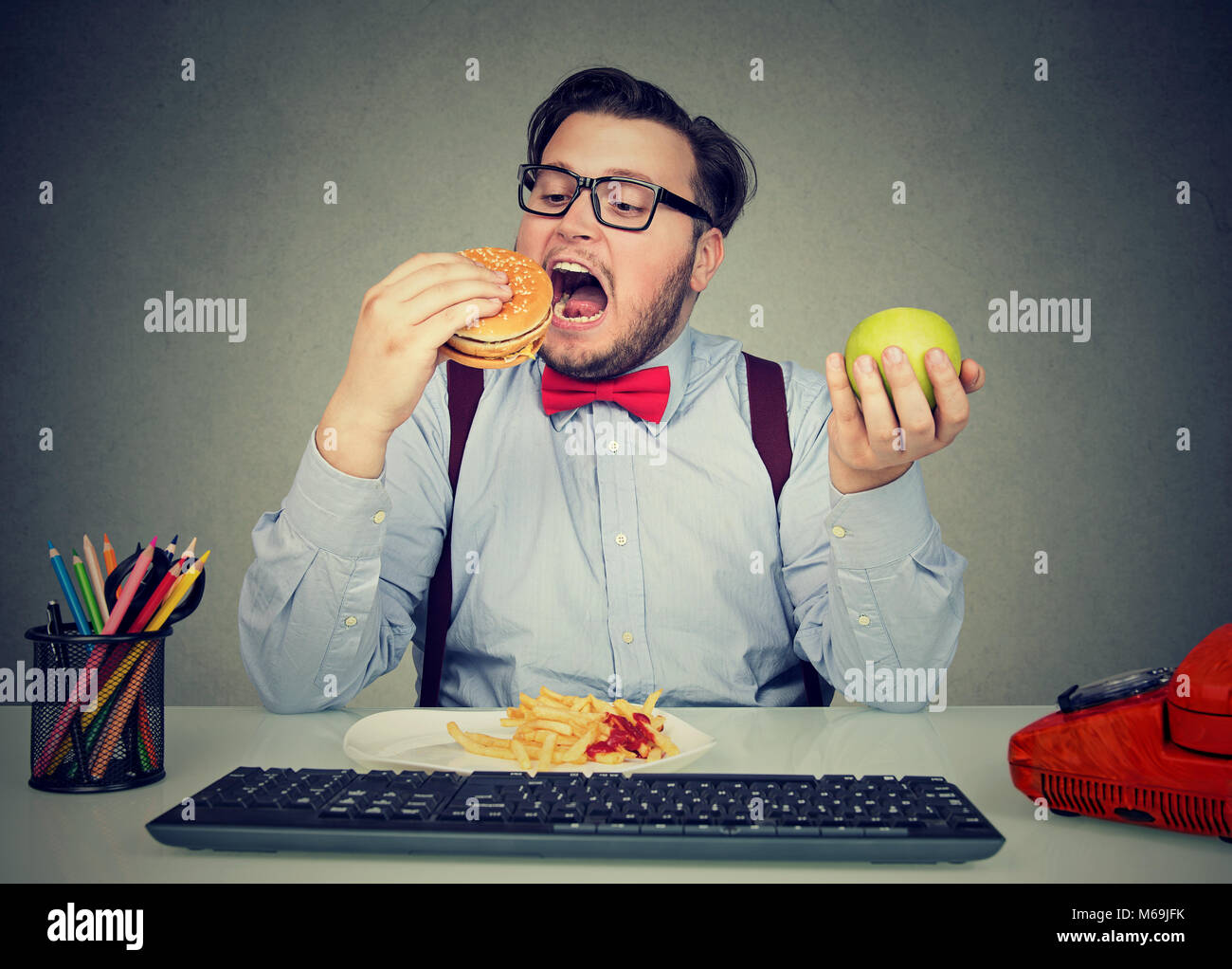 Young man eating hamburger with fries instead of apple having sedentary way of life in office. - Stock Image