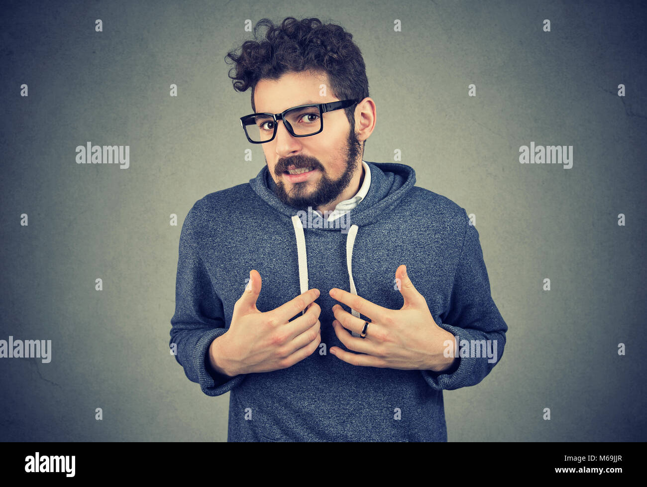 Young bearded man pointing at himself feeling guilty in awkward situation and looking at camera on gray. - Stock Image