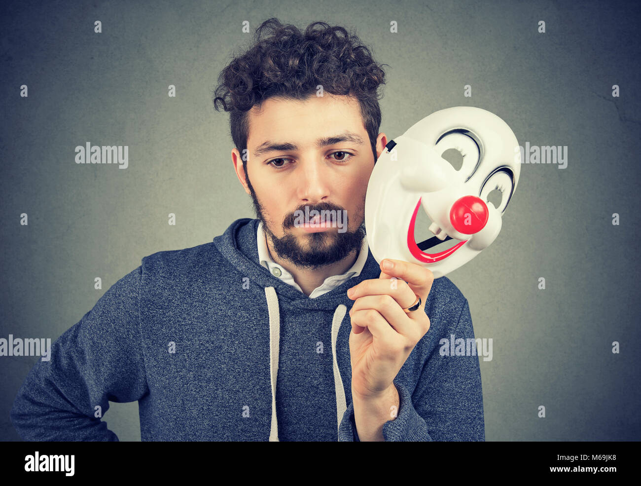 Young bearded upset man covering personality with happy clown mask on gray background. - Stock Image