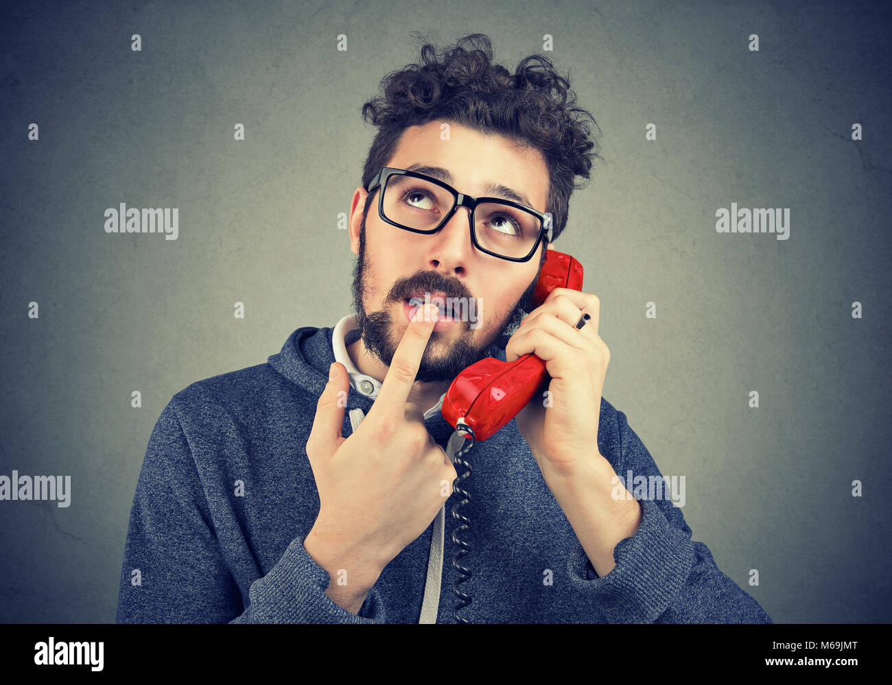 Young casual man looking up in confusion while talking on telephone against gray backdrop. - Stock Image