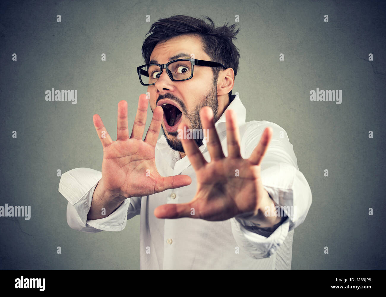 Young scared man in shirt holding hands in front of face and screaming in panic. - Stock Image