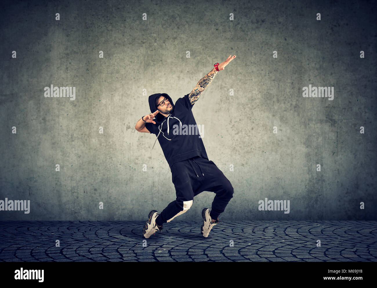 Stylish young man in trendy sportive clothing performing street dance with expression on gray background. - Stock Image