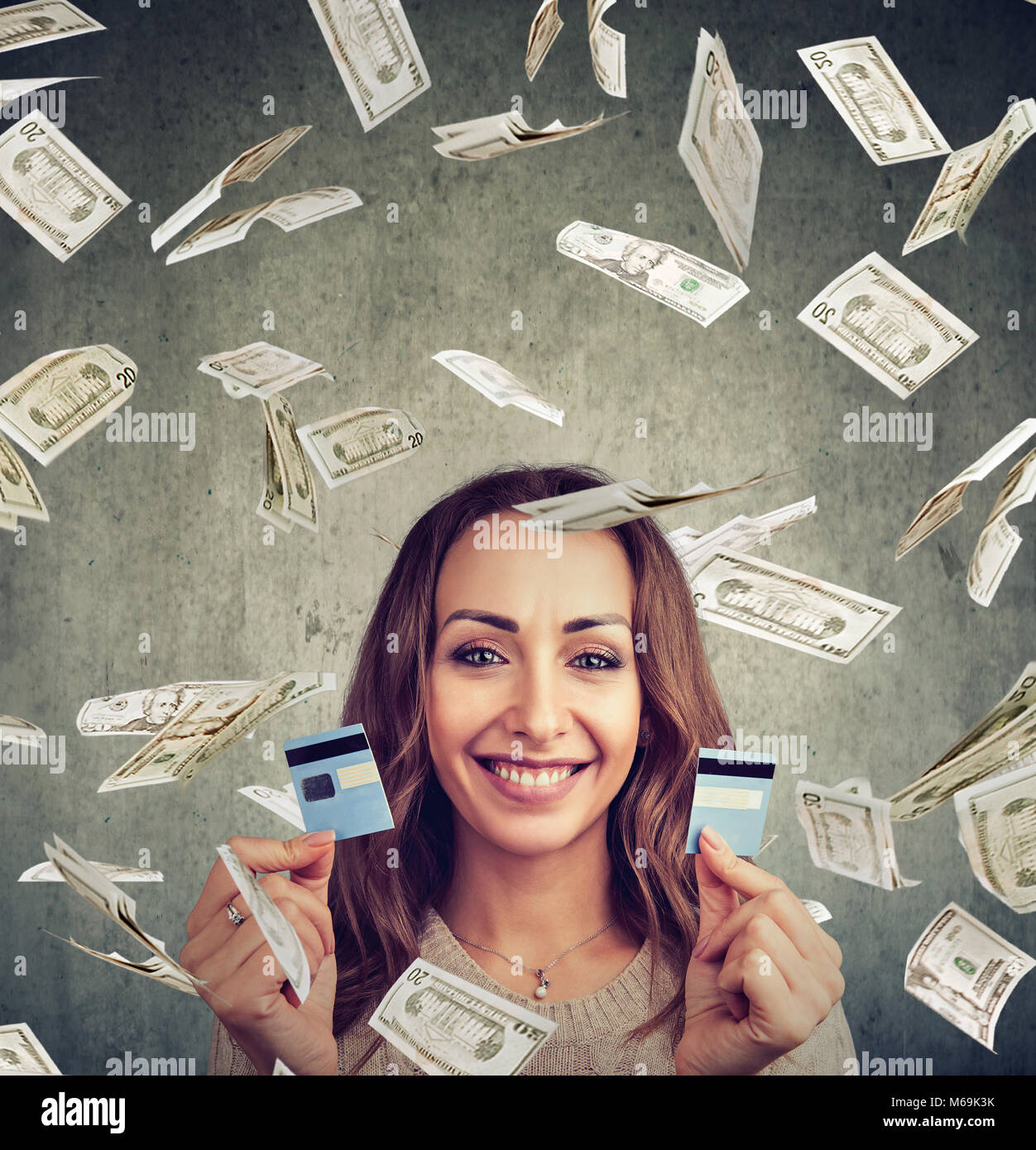 Happy debt free woman holding a credit card cut in two pieces under money rain - Stock Image