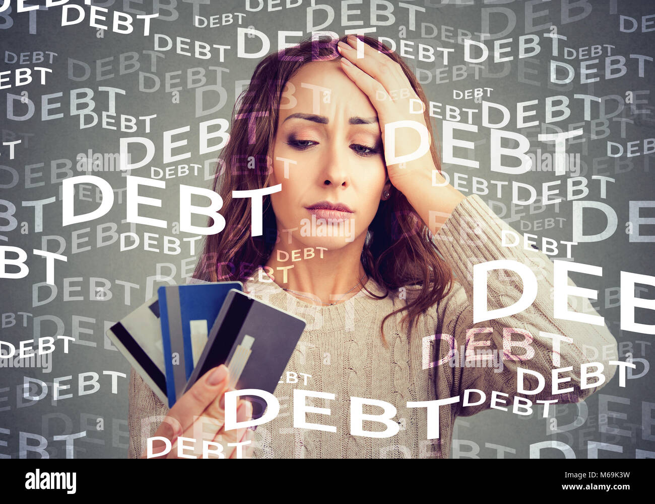 Concerned woman looking at many credit cards scared with huge amount of debt. - Stock Image