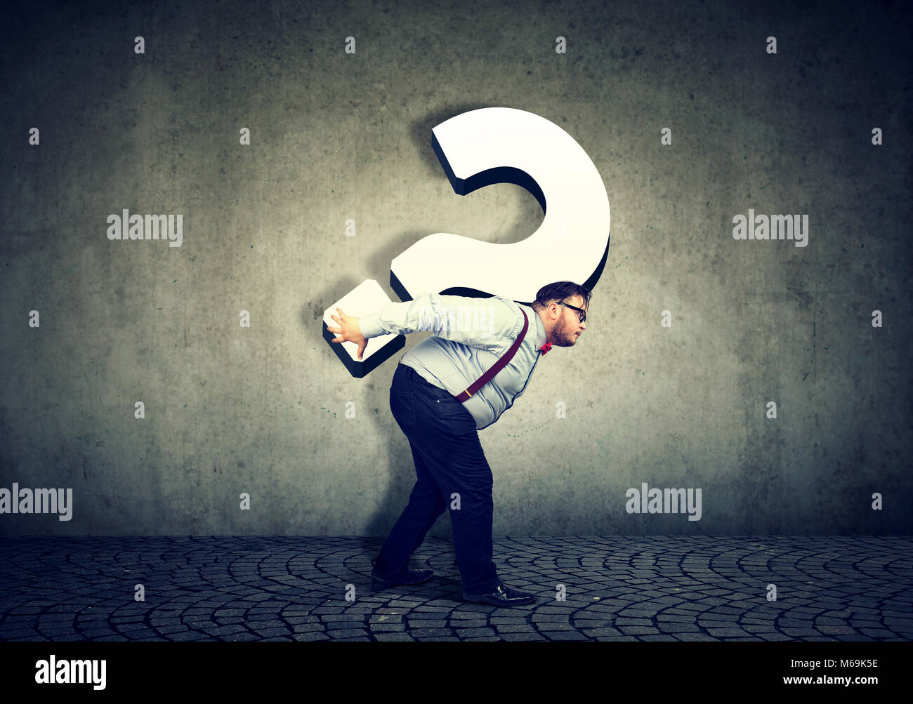Overworked business man carrying big question mark - Stock Image