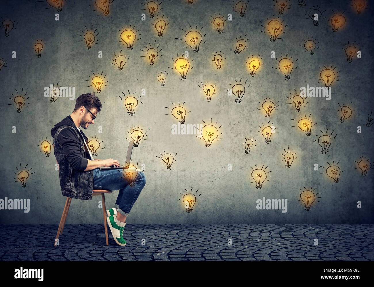 Young happy man entrepreneur working on laptop computer has plenty of successful ideas. - Stock Image