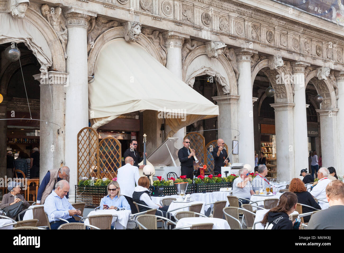 Musicians playing classical music outside the Caffe Chioggia in Piazza San Marco, Venice, Italy as tourists sit - Stock Image