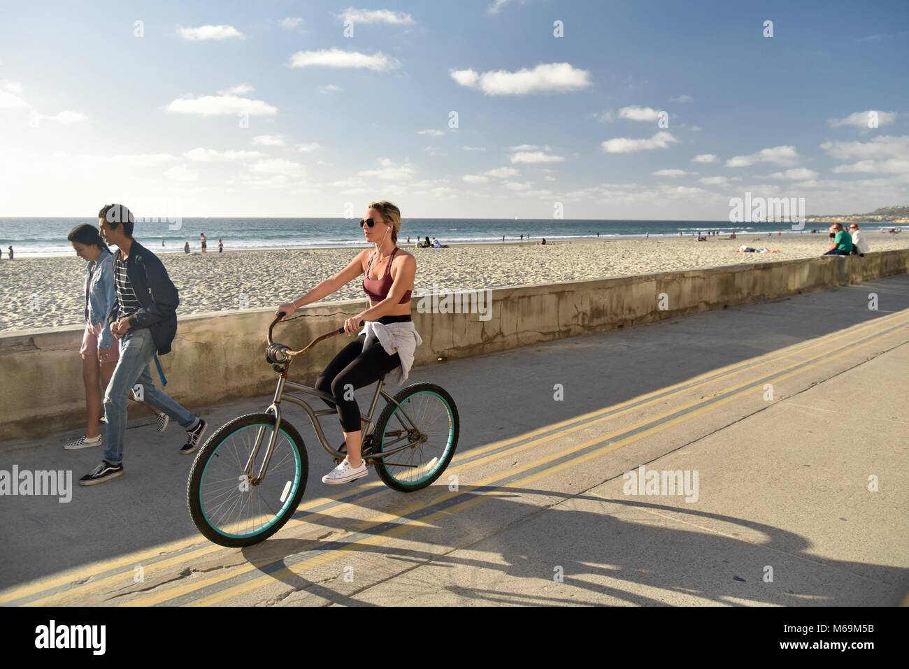 Attractive woman wearing sunglasses, pedaling bicycle along popular beachside paved boardwalk in Mission Beach, Stock Photo