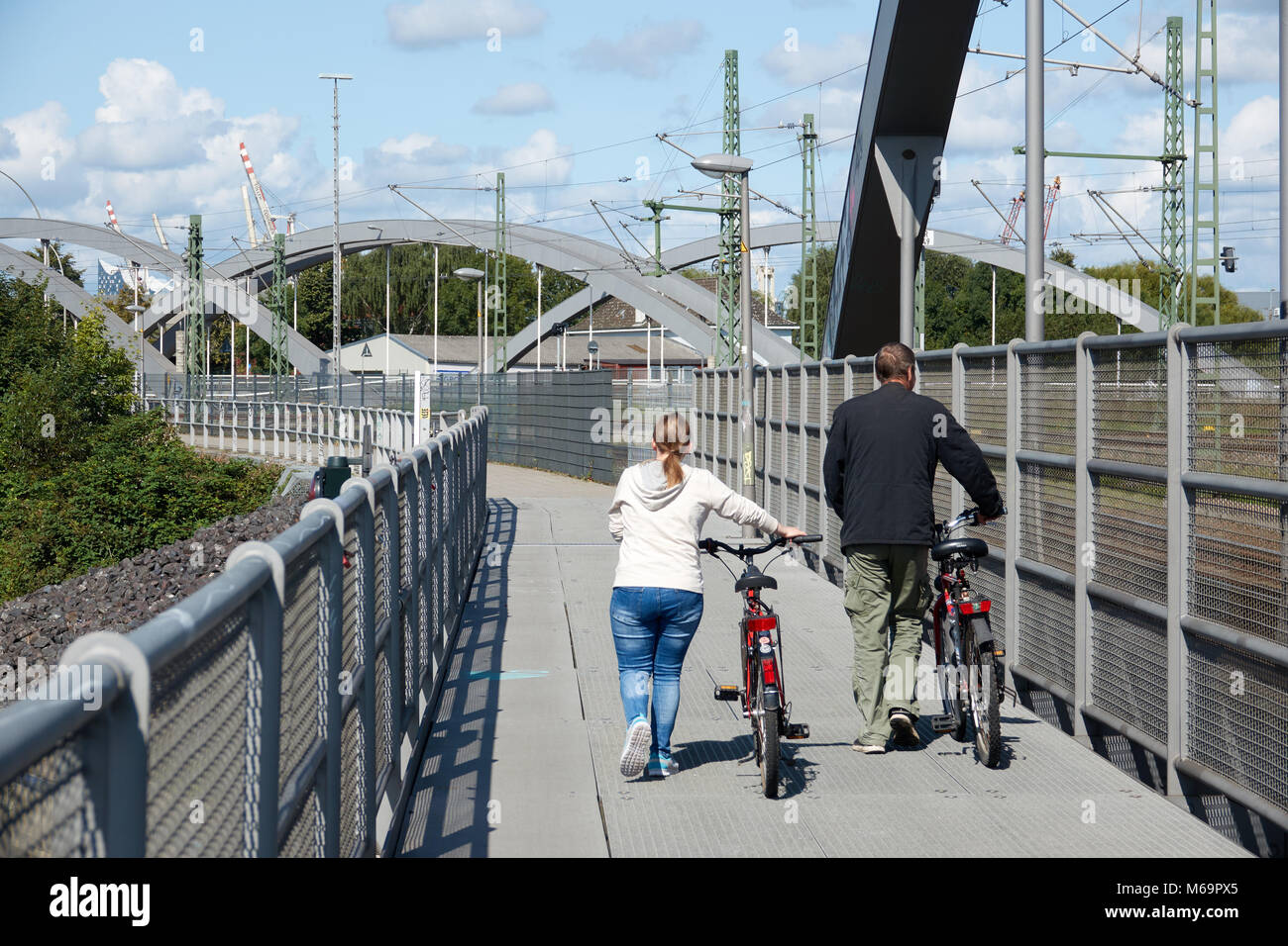 A married couple walking with bicycles on a bridge. - Stock Image