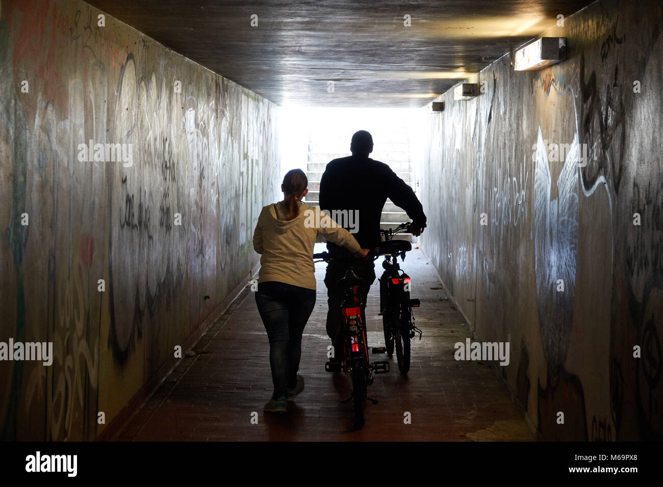 A man and a woman with bicycles walk along the underground passage. - Stock Image