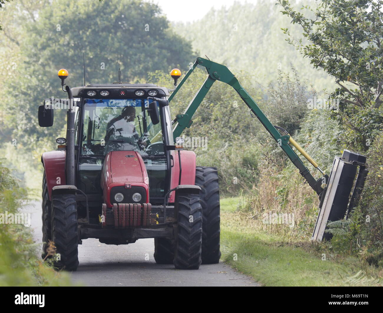 HEDGE TRIMMIMG USING TRACTOR POWERED TRIMMER IN RURAL LANE NEAR STALHAM, NORFOLK,ENGLAND UK - Stock Image