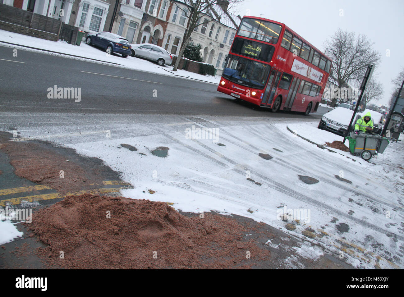 London, UK. 1st Mar, 2018. A council worker prepares grit for the footpaths along Romford Road after heavy overnight - Stock Image