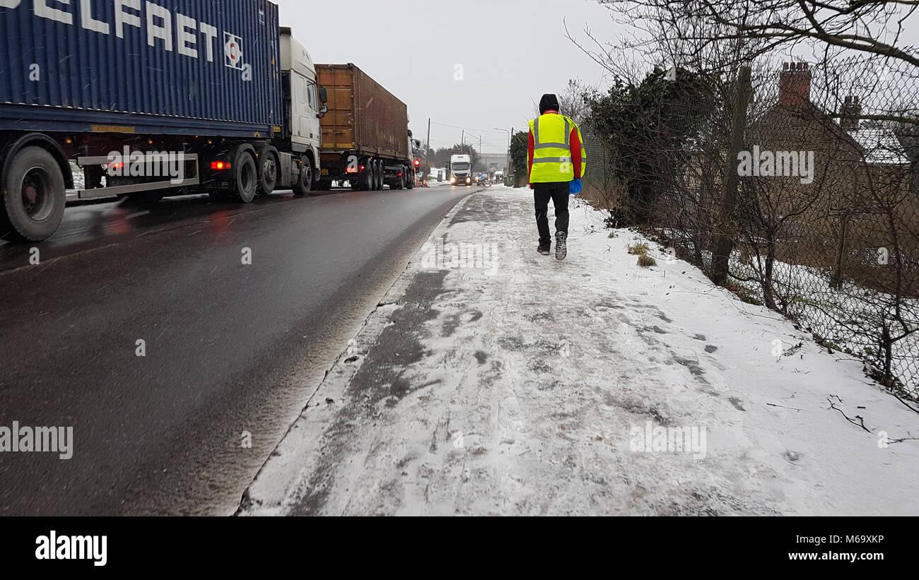 Purfleet, UK - March 1: A man walks along a snowy path on London Raod alongside a convoy of trucks following heavy - Stock Image