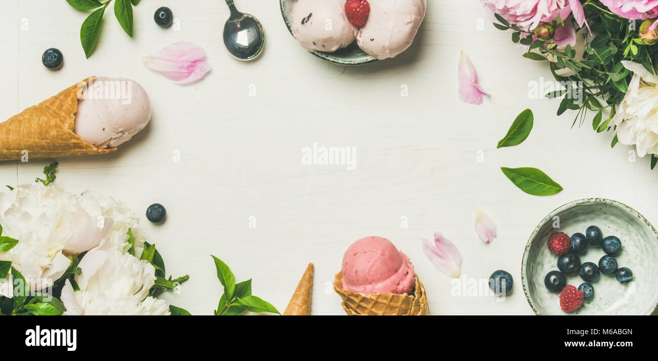 Flat-lay of ice cream scoops and peonies, wide composition - Stock Image