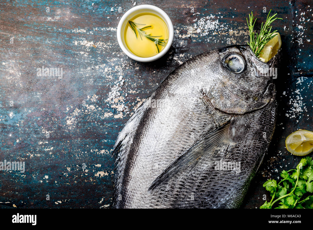 Food background with raw fresh fish reineta, herbs, olil and lemon. Top view. - Stock Image