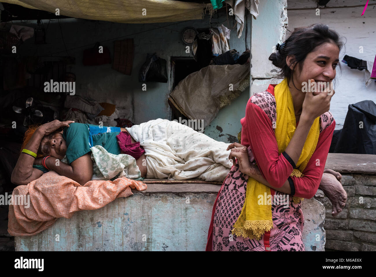 An ailing matriarch and her giggling family member in a courtyard in Varanasi, India. - Stock Image