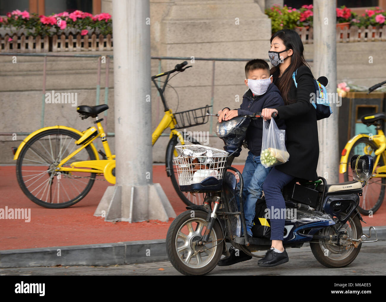 Shanghai, China - November 18, 2017:  Chinese woman and boy, wearing masks, ride a motorized bike on the streets - Stock Image