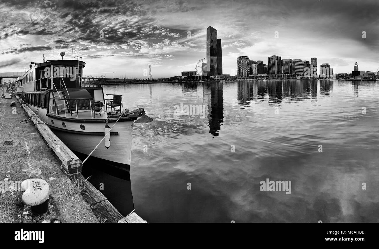 Moody charming panorama of Melbourne Docklands area with docked historic wooden boat and distant modern urban towers - Stock Image