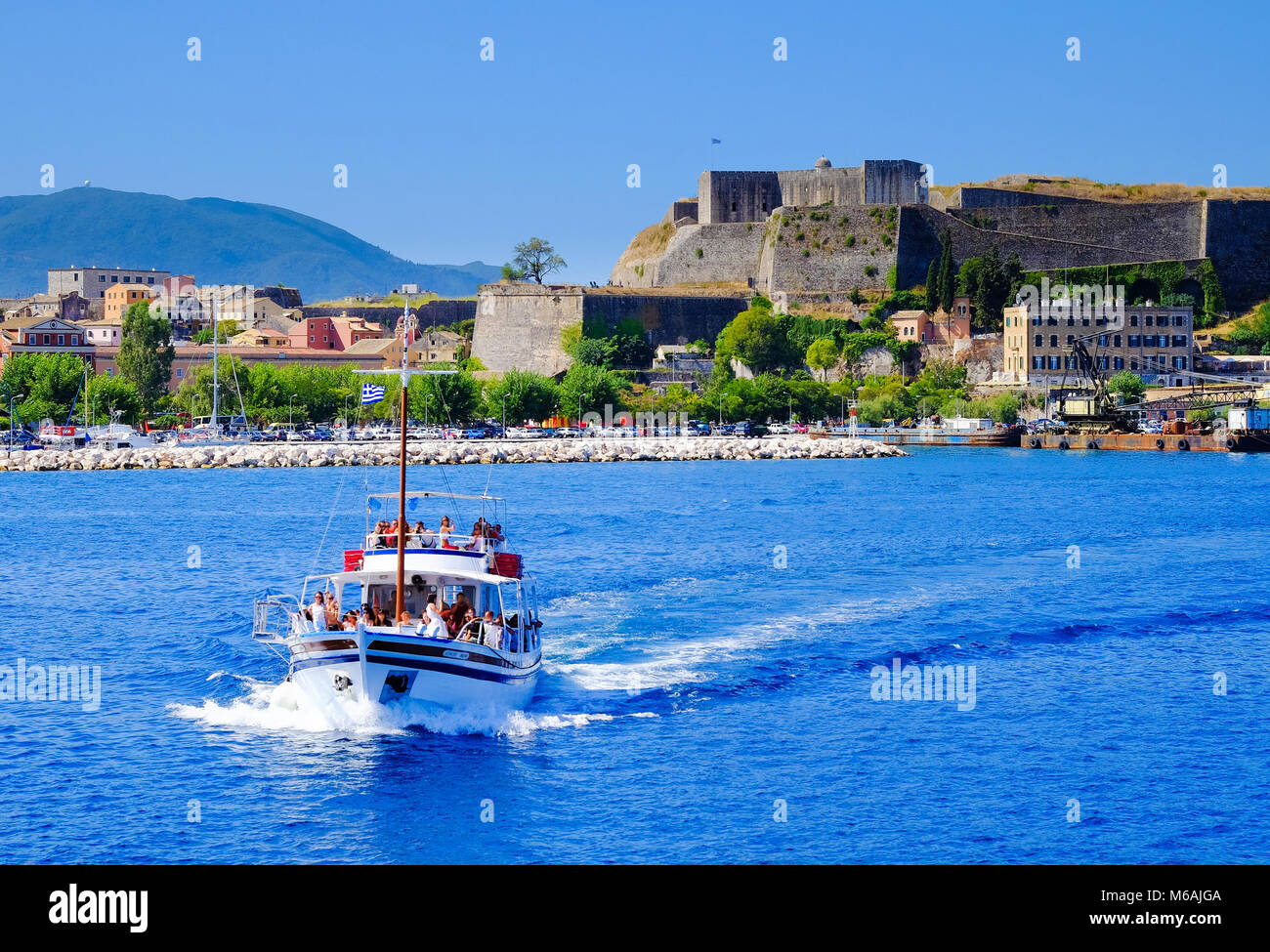 Boat sailing in daily trips around Corfu island with the old venetian fortress walls in the background. - Stock Image