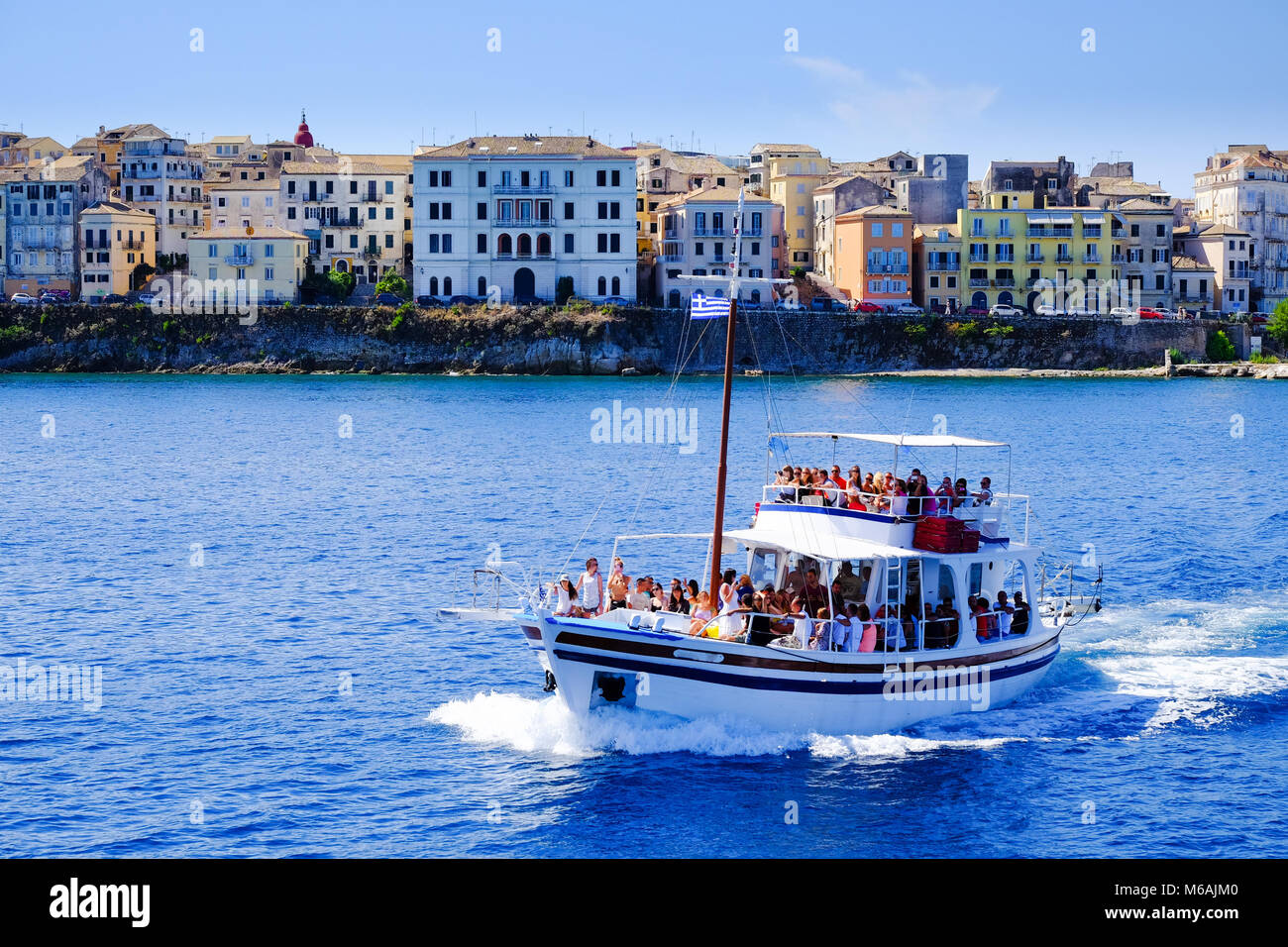 Boat sailing in daily trips around Corfu island with the old city in the background. - Stock Image