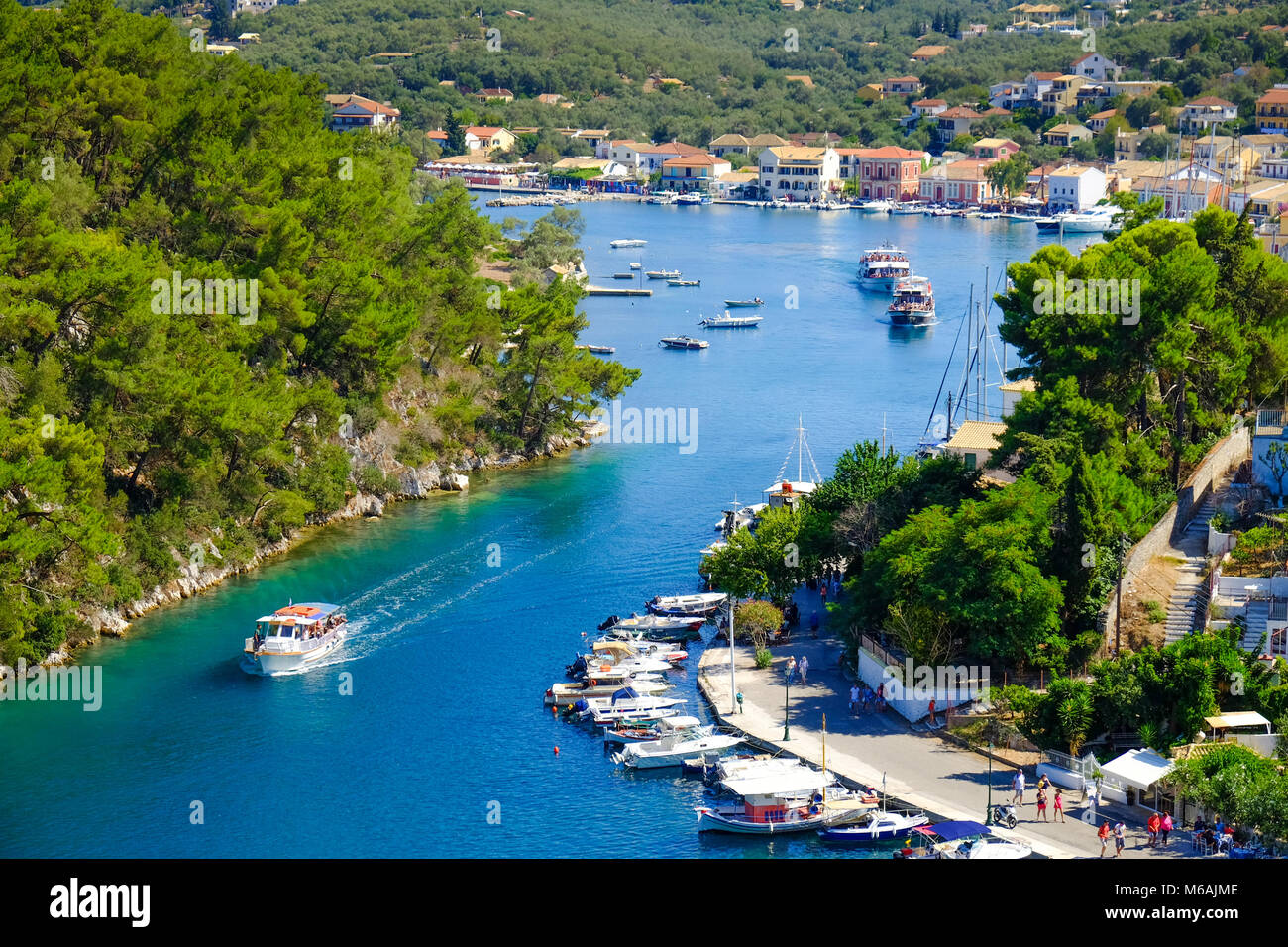 Old harbour of Paxos island with boat entering the grand canal - Stock Image