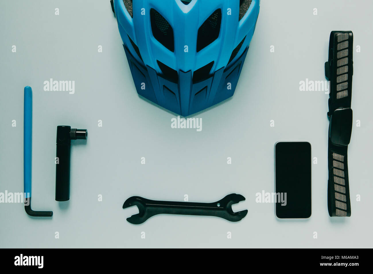 Cycling equipment and mobile phone on blue background. - Stock Image