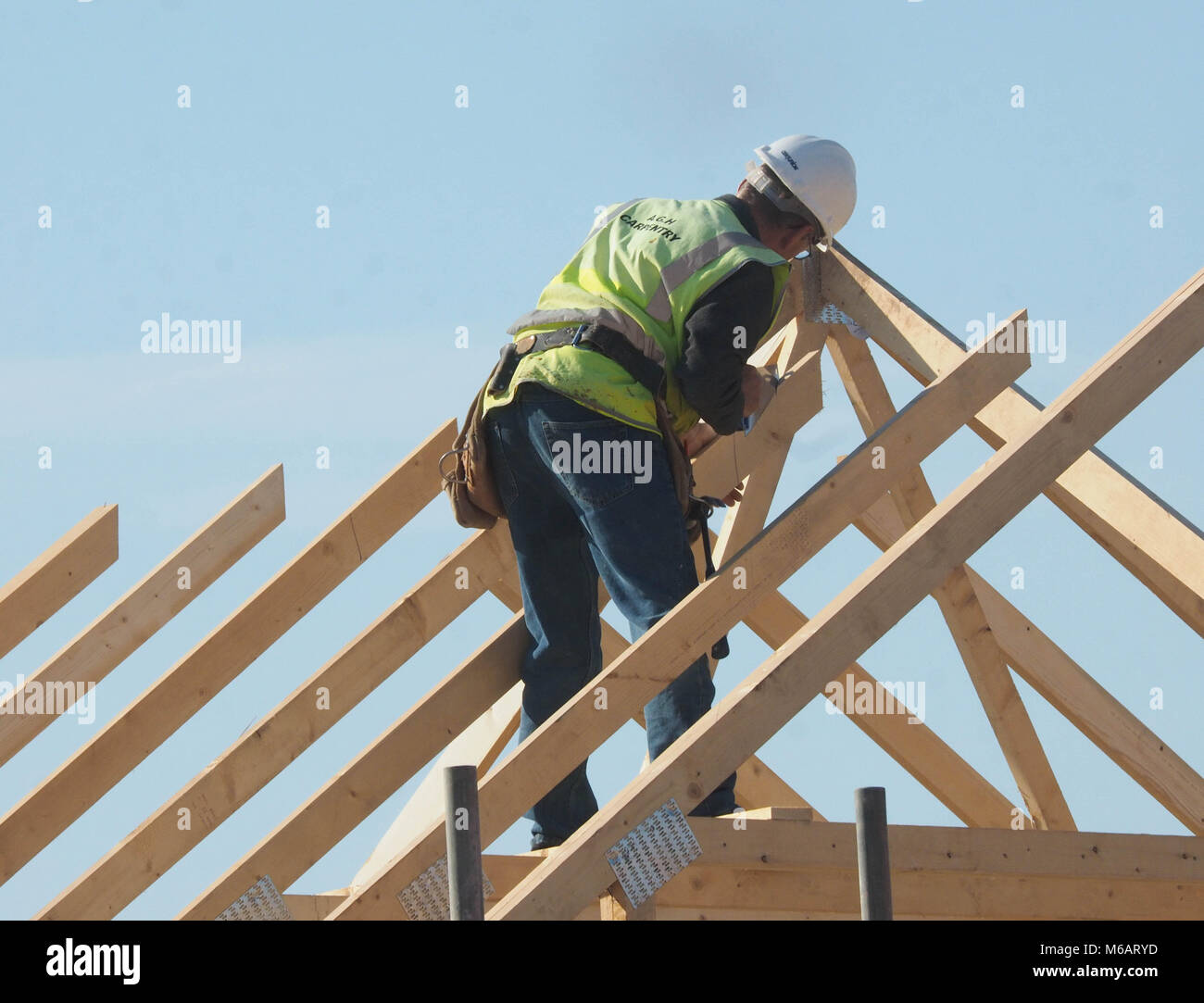 CARPENTER WORKING ON WOODEN ROOF TRUSSES ON BUILDING SITE IN NORFOLK, ENGLAND UK - Stock Image
