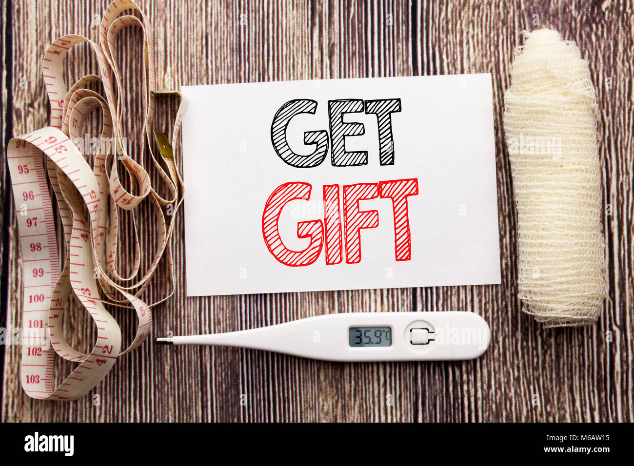 Handwritten text showing Get Gift. Business fitness health concept writing for Free Shoping Coupon written on wood - Stock Image
